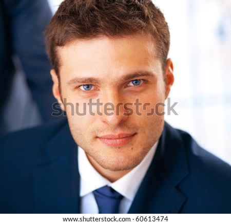 Closeup portrait of smiling young businessman working at the office.