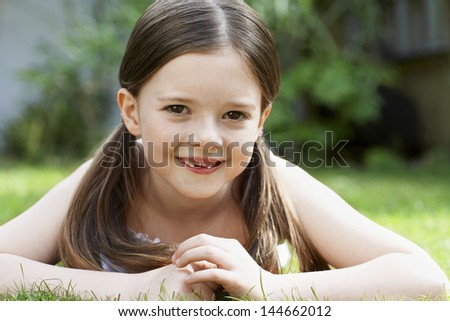 Closeup portrait of smiling young girl lying in grass - stock photo