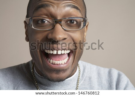 Closeup portrait of surprised young man wearing glasses on colored background - stock photo