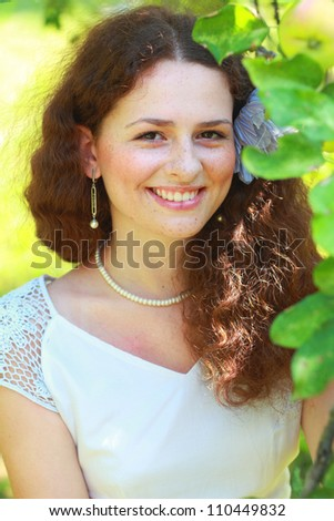 Closeup portrait of sweet teenage girl smiling under apple tree