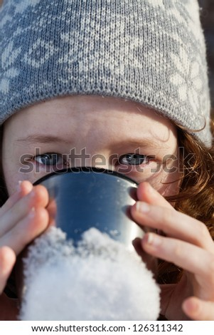 closeup portrait of teenager girl in winter hat drinking from flask cup - stock photo