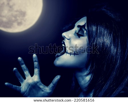Closeup portrait of terrifying witch yelling in full moon, aggressive woman with spooky makeup screaming in Halloween holiday  - stock photo