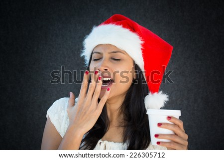 Closeup portrait of tiered sleepy woman in Santa Claus hat, hand on mouth yawning, holding a coffee cup,boring holiday, isolated on grey black background. facial expressions, attitude - stock photo