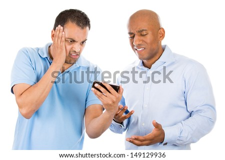 Closeup portrait of two guys looking upset while watching something on their cell phone, a text message, sms or email, isolated on white background - stock photo