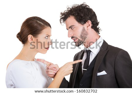 Closeup portrait of two people, man and woman, couple pointing fingers at each other, blaming each other for the problem, isolated on white background. Marriage difficulties concept. Negative emotions - stock photo