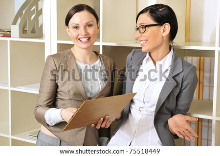 Closeup portrait of two pretty cheerful business women in an office environment - stock photo