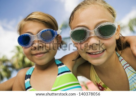Closeup portrait of two smiling girls wearing swim goggles - stock photo
