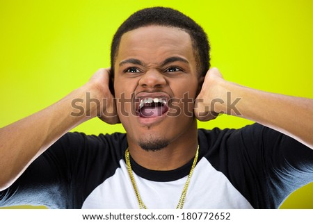 Closeup portrait of upset, frustrated, overwhelmed, stressed young man squeezing his head, going nuts, screaming, losing mind, isolated on green background. Negative emotion facial expression feelings