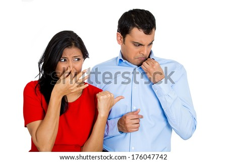 Closeup portrait of woman looking at man closing, covering nose, something stinks, very bad smell, odor. Guy sniffs himself. Isolated on white background. Negative emotion, facial expression, feeling - stock photo