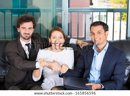 Closeup portrait of woman trying to force a deal and handshake between two men of different races sitting on black couch in apartment, home or office, isolated on a city urban background - stock photo