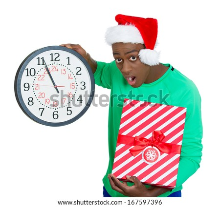 Closeup portrait of worried young man wearing red santa claus hat, holding clock and gift in hands, isolated on white background. Negative emotion facial expression. Last minute holiday shopping - stock photo