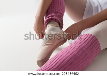 Closeup portrait of young and beautiful modern style ballet dancer warming up, isolated on white background, studio shot - stock photo