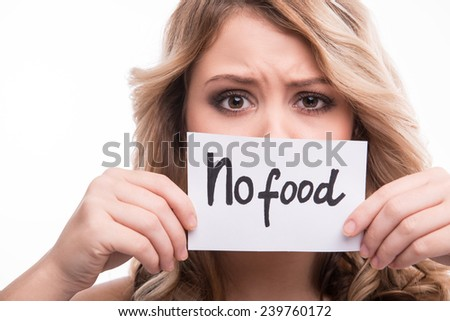 Closeup portrait of young attractive woman holding prohibition card with no food notice isolated on white background, diet concept - stock photo