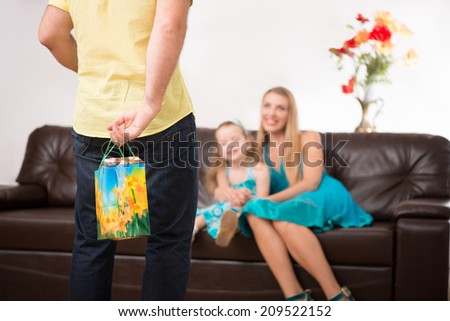 Closeup portrait of young beautiful family, father hiding present behind back at home and smiling mother and daughter sitting on sofa, selected focus - stock photo