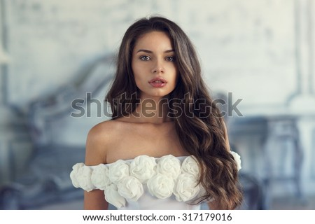 Closeup portrait of young beautiful pretty cute girl in evening dress posing in luxury interior and looking at you. Fashion photo - stock photo