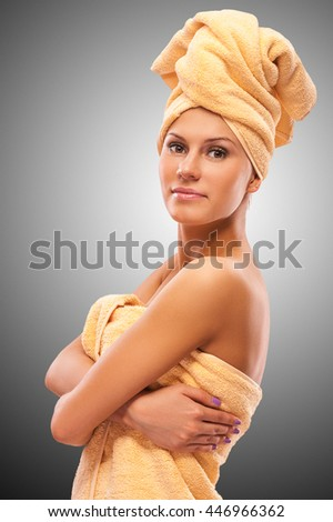 Closeup portrait of young beautiful woman after bath, on grey background.