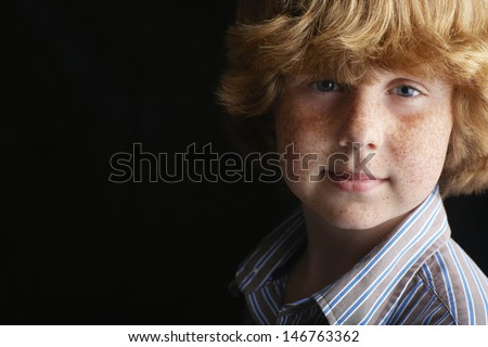 Closeup portrait of young boy isolated on black background - stock photo