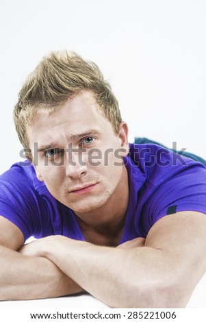 Closeup Portrait of Young Caucasian Handsome Tanned Man Laying Down with Hands Folded in Front. Vertical Image Orientation - stock photo