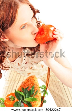 Closeup portrait of young caucasian woman with straw basket of fresh vegetables wearing trendy clothes isolated on white background. Eating her harvest