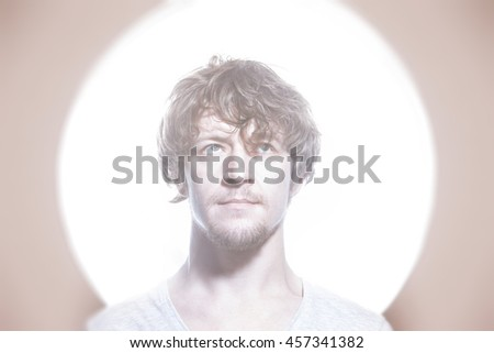 Closeup portrait of young creative man at bright circle light background. Concept of innovation, ideas. - stock photo