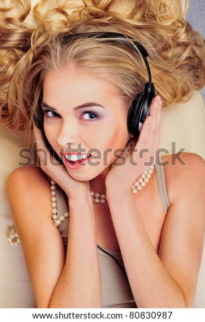 Closeup portrait of young cute girl with beautiful curly hair listen to music on a sofa - stock photo