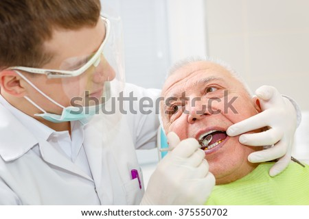 Closeup portrait of young dentist treating senior elderly man - stock photo