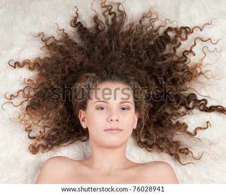 Closeup portrait of young emotional beautiful girl with perfect curly hair. Lying on white fur bed - stock photo