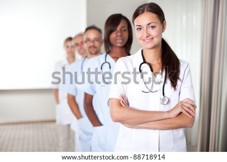 Closeup portrait of young female doctor smiling at the camera with colleagues - stock photo