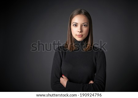 Closeup portrait of young female in black pullover with  folded hands with a speculative look on her face looking at the camera, over dark studio background - stock photo