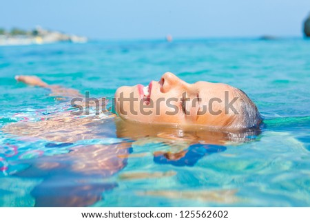 Closeup portrait of young girl swimming in the transparent sea - stock photo
