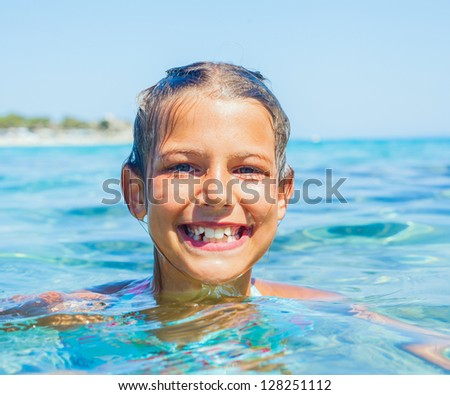 Closeup portrait of young girl swimming in the transparent sea