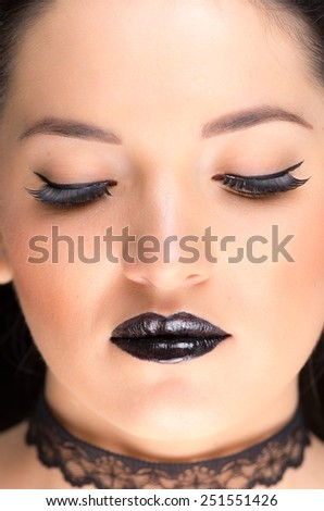 closeup portrait of young gothic beautiful woman with black makeup - stock photo