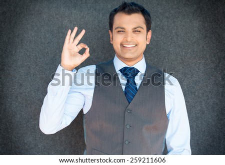 Closeup portrait of young handsome happy, smiling excited man giving OK sign with fingers, isolated gray background. Positive human emotions, facial expressions, feelings, symbols, body language - stock photo