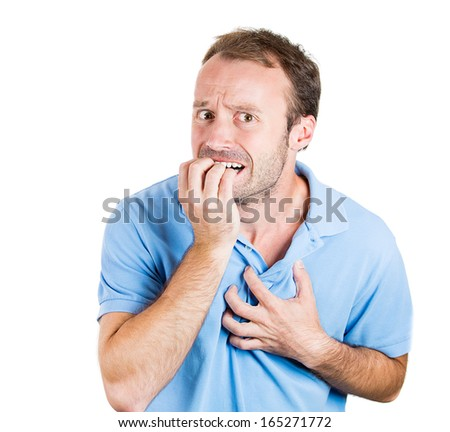 Closeup portrait of young handsome man in blue shirt hand in mouth and on chest very anxious tense in anticipation of something isolated on white background. Negative human emotion facial expression - stock photo