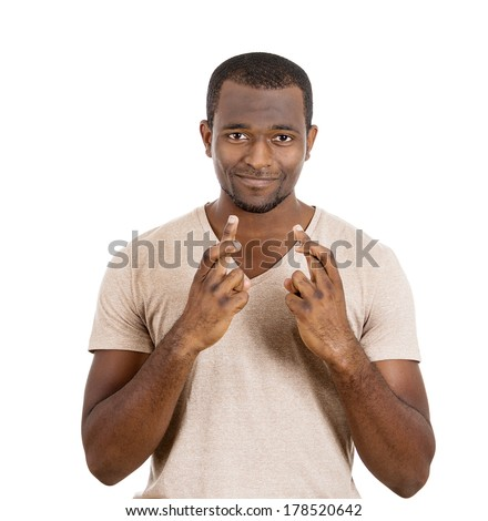 Closeup portrait of young handsome smiling man, crossing fingers wishing, praying for miracle, hoping for best, isolated on white background. Positive human emotion facial expression feelings attitude