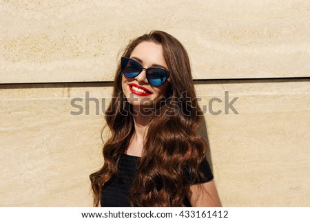 Closeup portrait of young happy smiling beautiful girl with long brunette curly hair posing against wall and smiling on a sunny warm day - stock photo