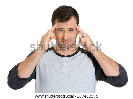 Closeup portrait of young man having really bad headache pain placing both hands on temples, isolated on white background. Negative human emotion facial expressions feelings