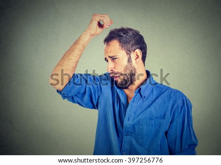 Closeup portrait of young man, smelling, sniffing his armpit, something stinks, very bad, foul odor situation, isolated on gray wall background. Negative emotion, facial expression, feeling - stock photo