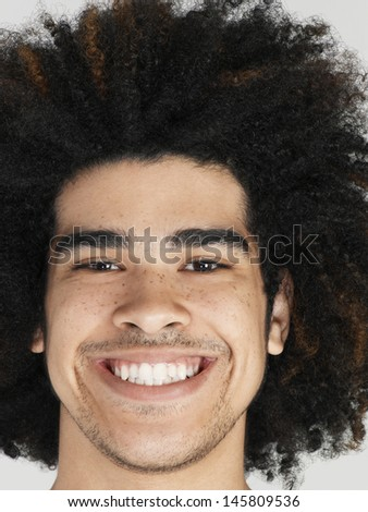 Closeup portrait of young man with afro hairdo smiling on colored background