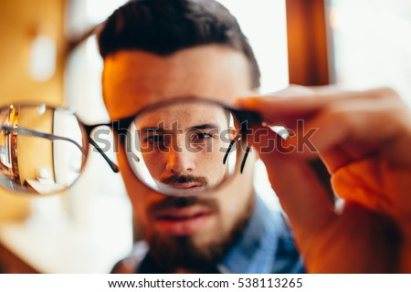 Closeup portrait of young man with glasses. He has eyesight problems and is squinting his eyes a little bit. Handsome guy is holding his eyeglasses right in front of camera with one hand