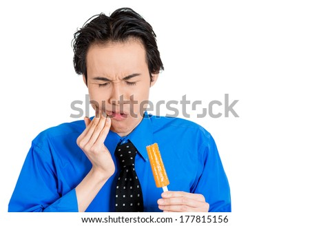 Closeup portrait of young man with sensitive tooth ache problem pain from cold frozen popsicle ice cream, hand on mouth, isolated white background. Negative human emotion, facial expressions, feelings - stock photo