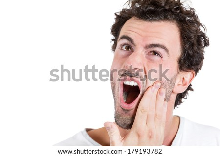 Closeup portrait of young man with tooth ache pain distress crown bridge problem  touching outside mouth with hand, isolated on white background. Negative human emotion facial expression feeling - stock photo