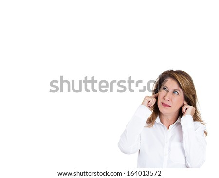 Closeup portrait of young, mature annoyed woman, covering her ears looking up, to the left, as if to say, stop making loud noise it's giving me headache, isolated on white background with copy space - stock photo