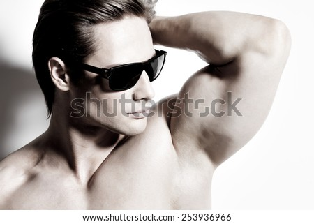 Closeup portrait of young muscular sexy man in glasses with hands behind head posing at studio as fashion model on a white background with contrast shadows. - stock photo