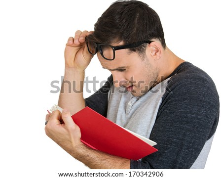 Closeup portrait of young nerdy guy with big black eye glasses trying to read book but having difficulties seeing text because of vision problems. Negative emotion facial expression feelings - stock photo