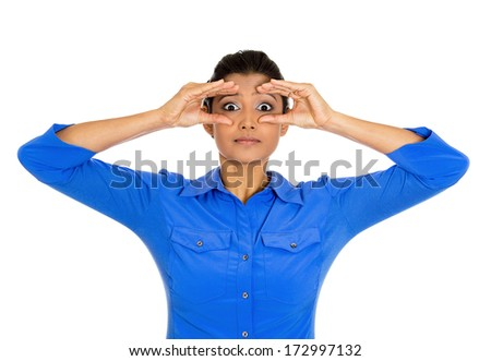 Closeup portrait of young pretty serious curious woman, peeking through her fingers like binoculars, searching for something, looking to the future, isolated on a white background. Sign, symbols - stock photo