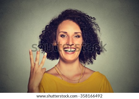 Closeup portrait of young pretty woman giving a three fingers sign gesture with hand isolated on gray wall background. Positive human emotions, facial expressions, feeling, symbols, body language  - stock photo