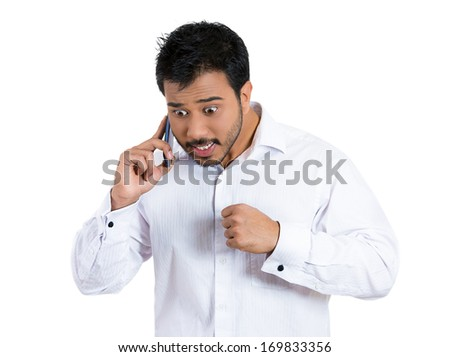 Closeup portrait of young, serious, angry business man, corporate employee, student talking on a cell phone, having unpleasant conversation, isolated on white background. Negative human emotions. - stock photo