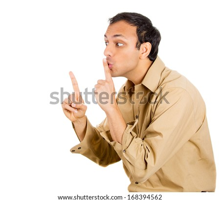 Closeup portrait of young serious man placing finger on lips as if to say, shhhhh, be quiet, silence , isolated on white background with. Negative facial expression, human emotions signs and symbols