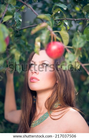 closeup portrait of young sexy pretty woman at apple tree on green outdoors copy space background - stock photo